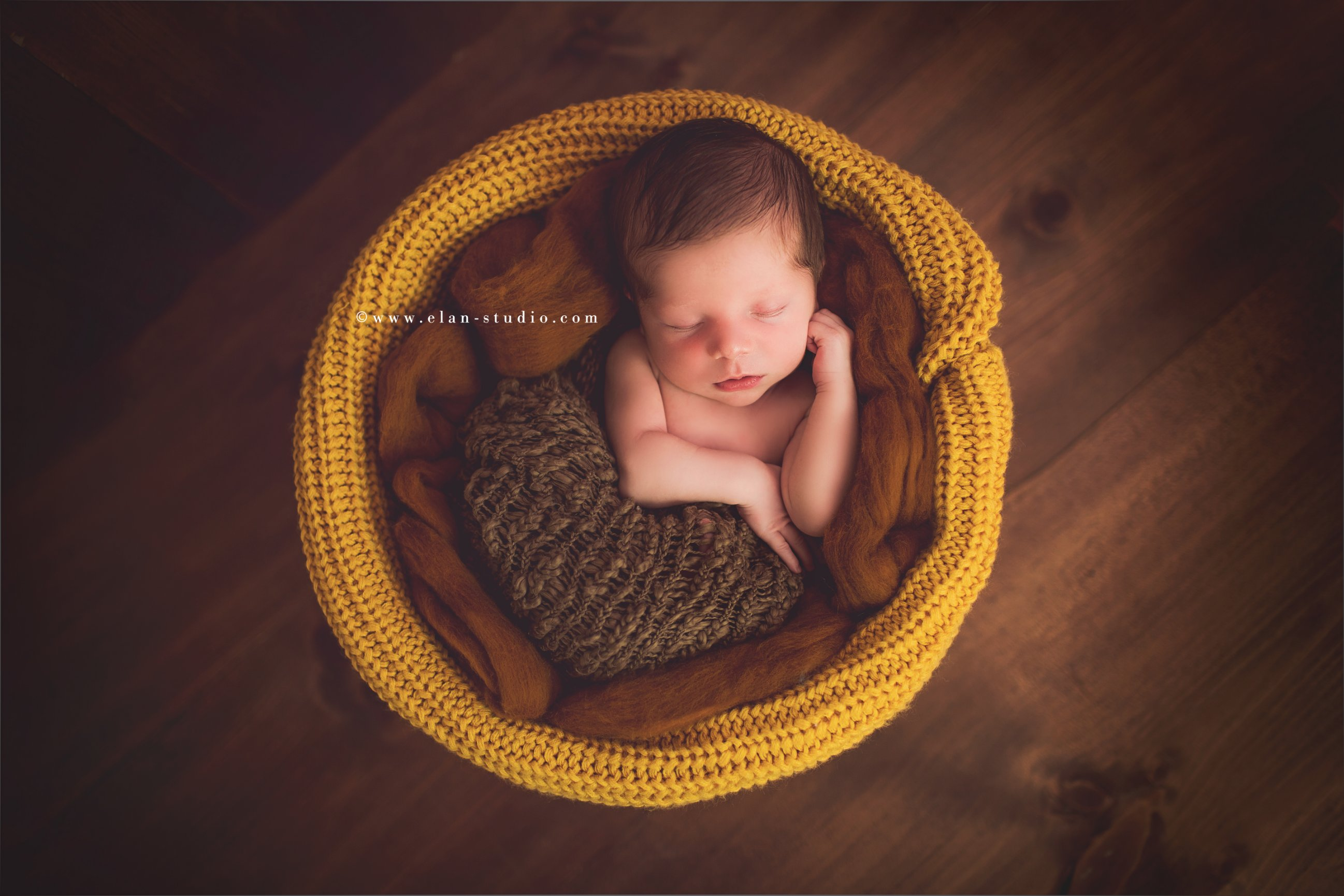 newborn baby wrapped in brown and mustard