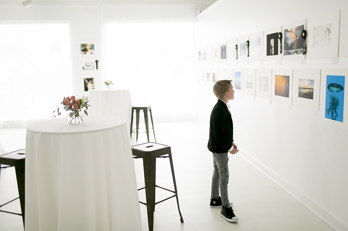 boy looking at framed photo gallery wall in white studio space