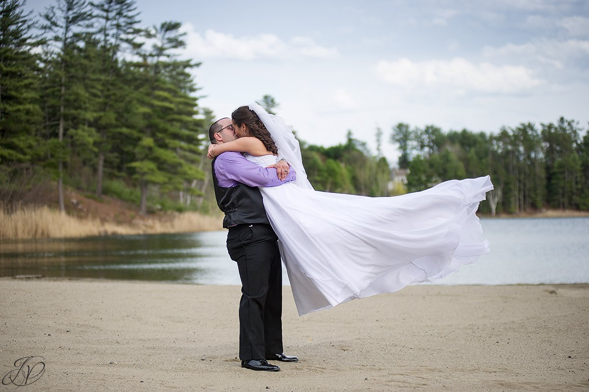photo of bride and groom twirling on beach