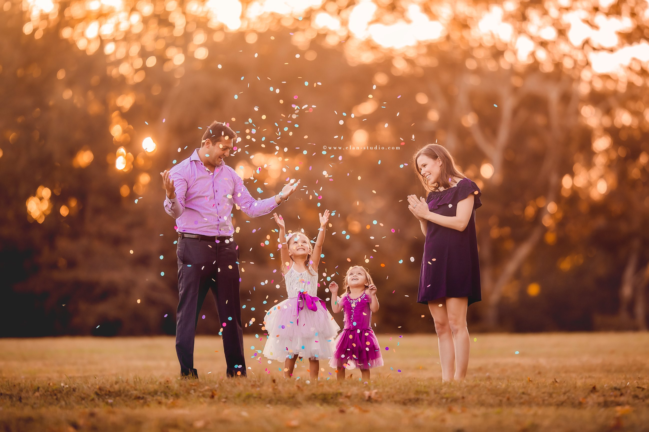 parents with two little girls throwing confetti