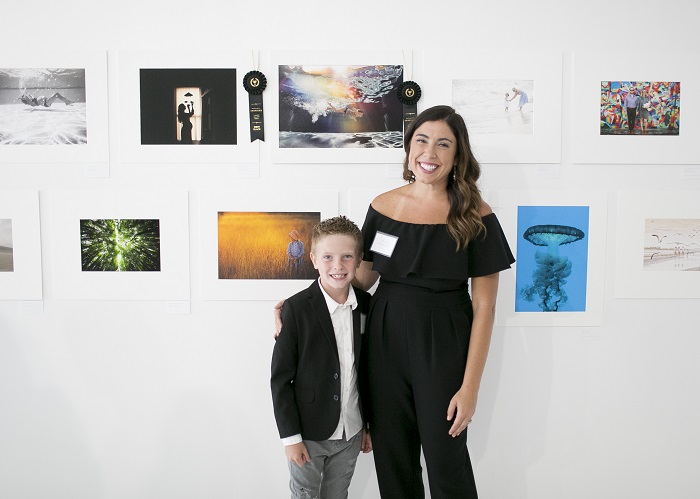 Tracy Sweeney and son in front of Inspired Gallery Event photo wall