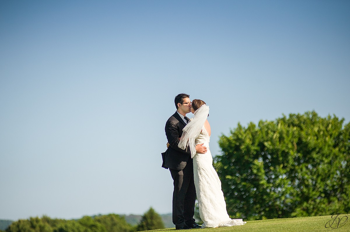 bride and groom kissing golf course photo