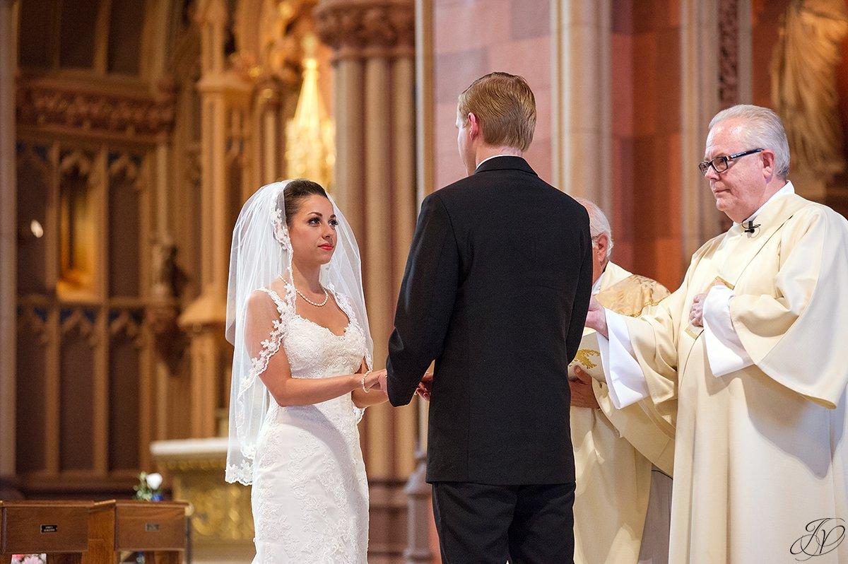 bride putting on groom's wedding band catholic church ceremony