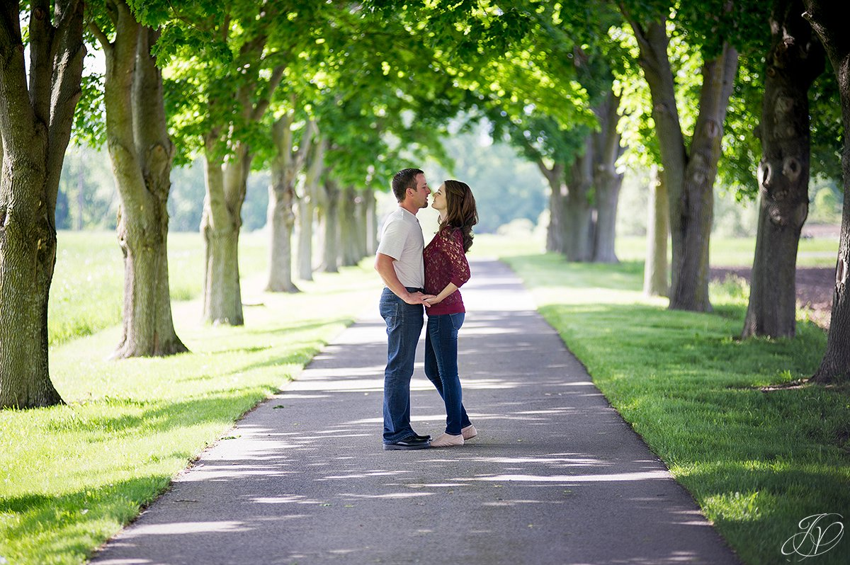 romantic couple kissing in row of trees