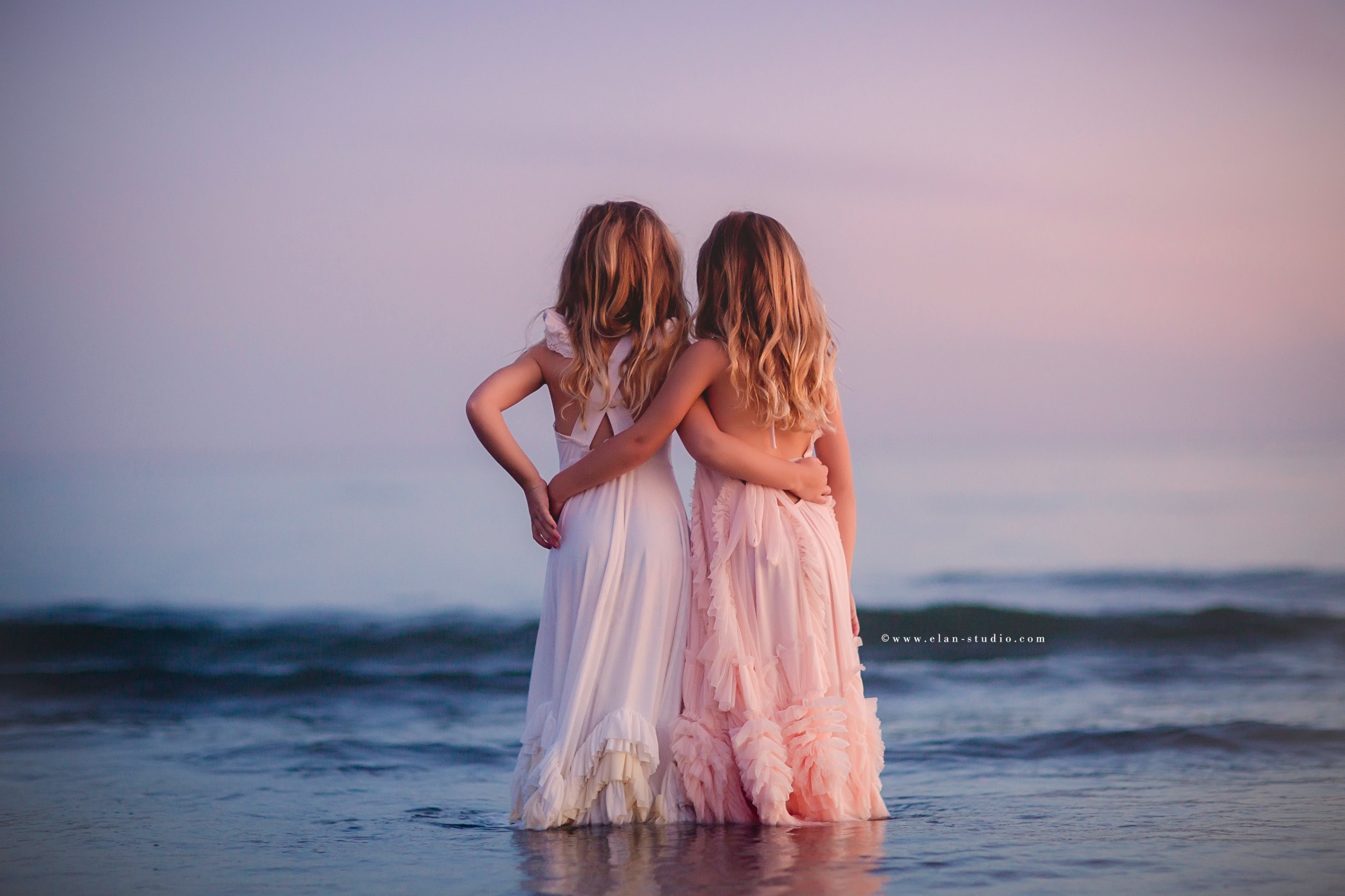 twin girls with arms around eachother, standing in ocean at sunset