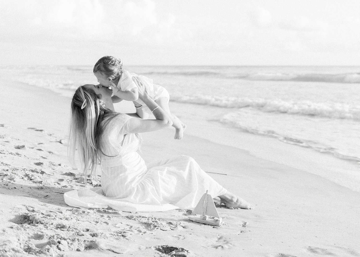 black and white photograph of a mother lifting up her baby boy to kiss him in the sand