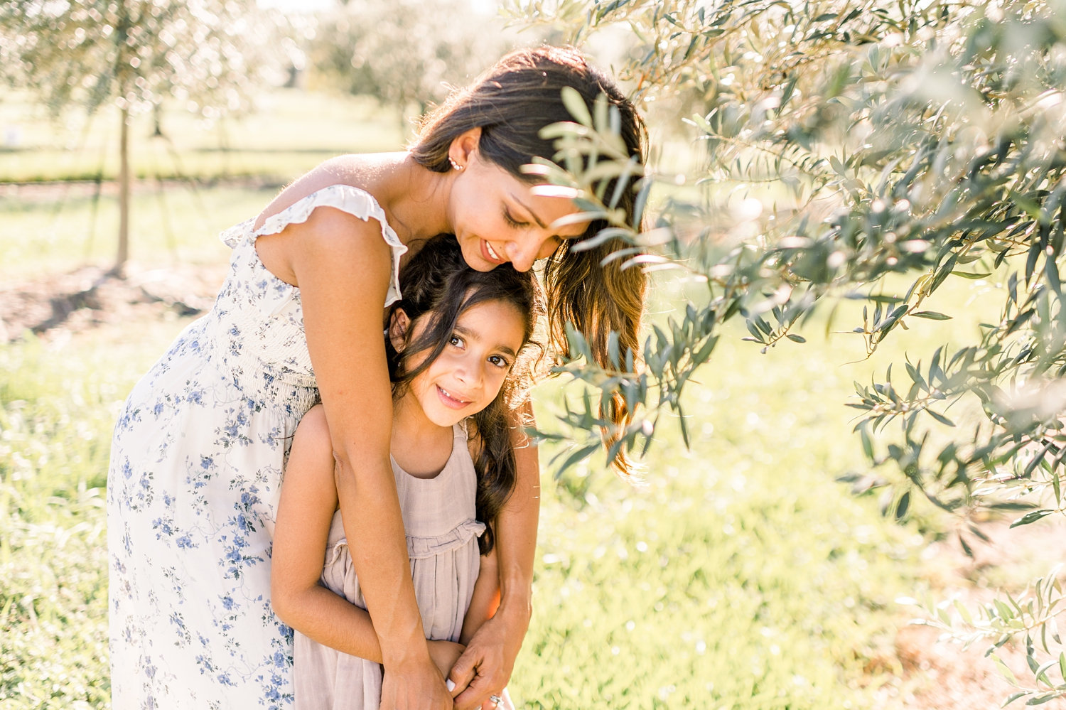 mother embracing daughter, girl looking at camera, olive tree, Florida, Ryaphotos