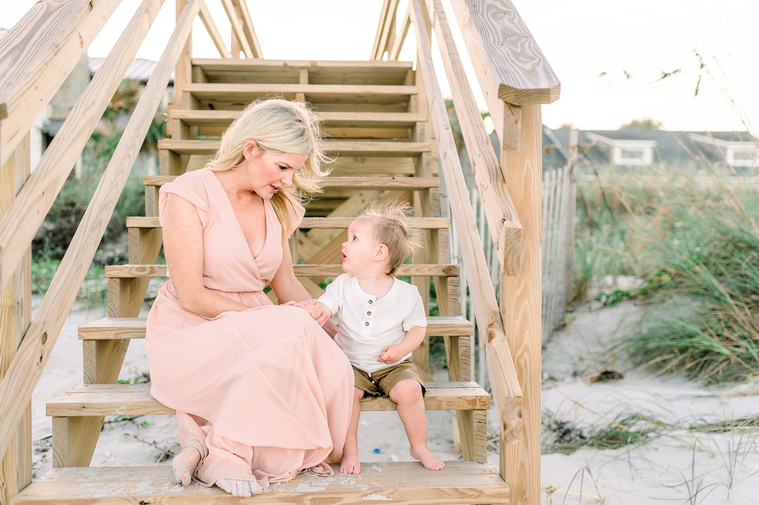 mommy and son sitting on wooden beach stairs, sandy feet, beach homes in background, Rya Duncklee
