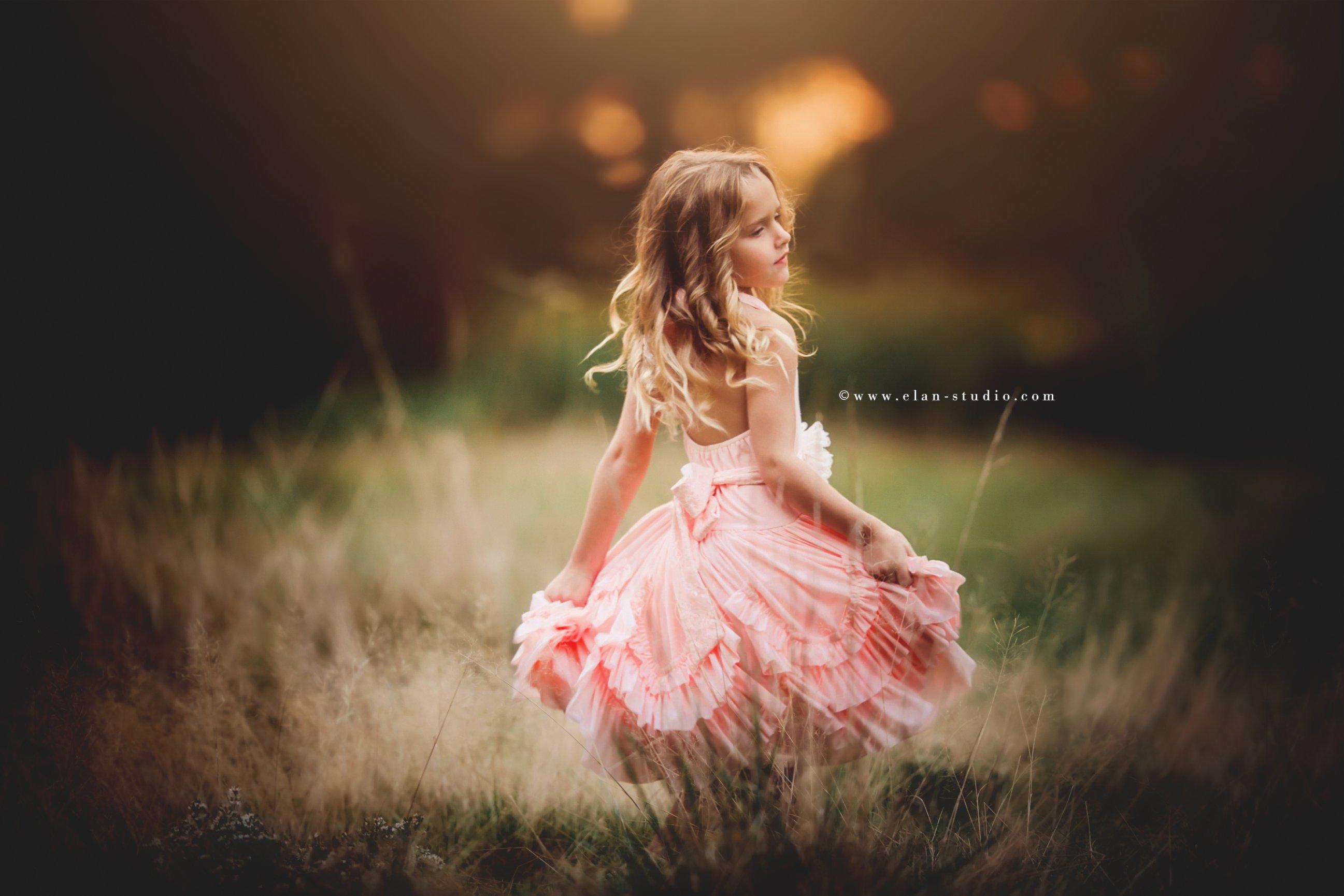girl twirling, pink dress, bokeh